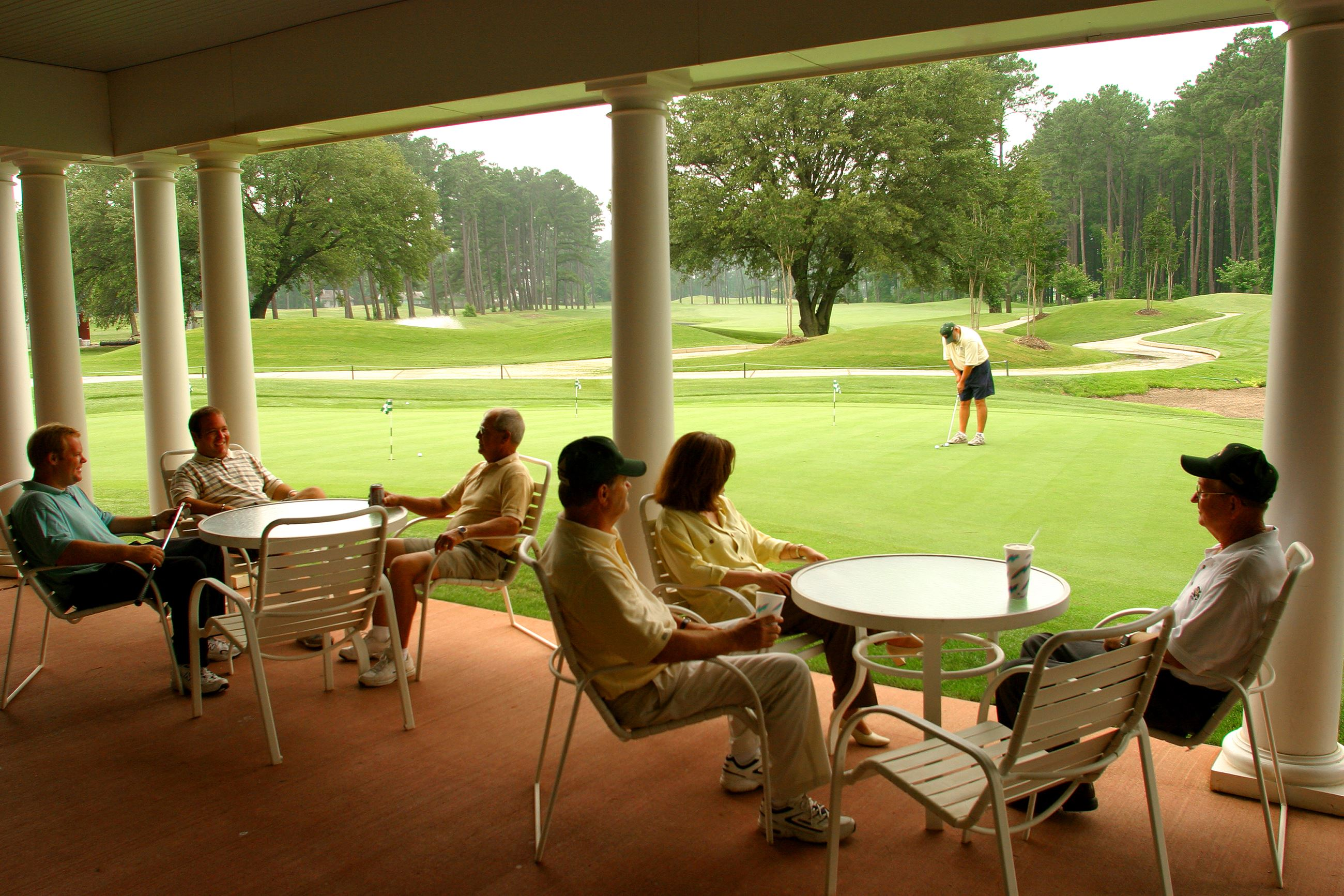 Golfers sitting under awning